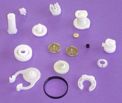 Miniature and Micro Injection Moulding - Selection of AKI's miniature mouldings compared to a 5p piece